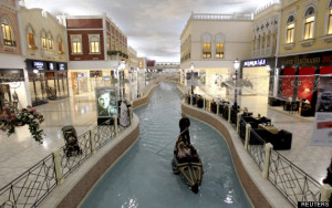 A family takes a sampan ride on a canal inside Villagio Mall, a popular shopping area in Doha